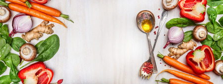 47925152 - organic clean vegetables assorted with cooking spoons and oil on white wooden background, top view, banner. healthy food, vegan or diet nutrition concept.